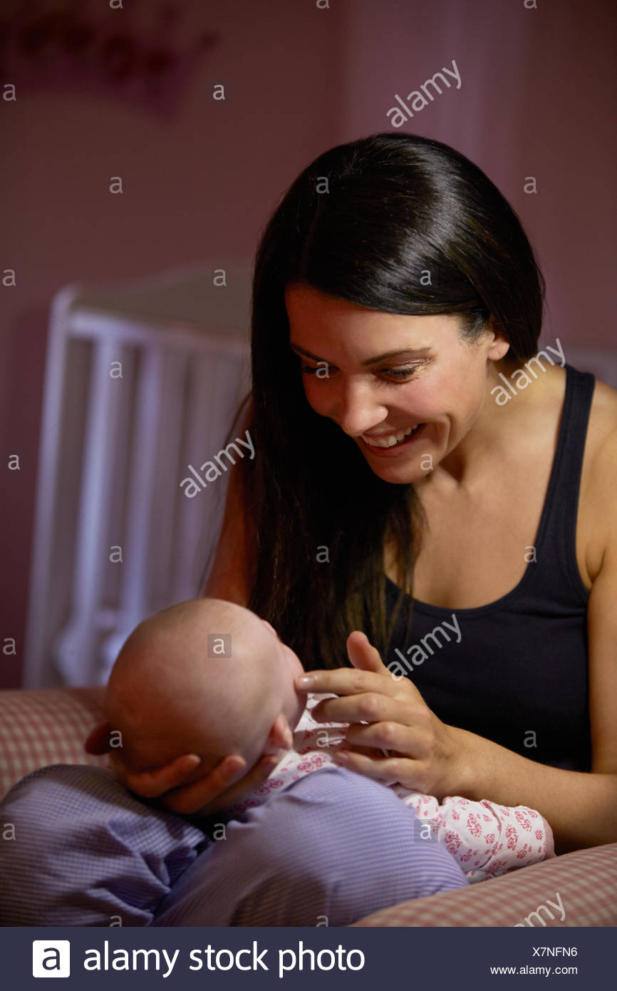Mother At Home Cuddling Newborn Baby In Nursery - Stock Image