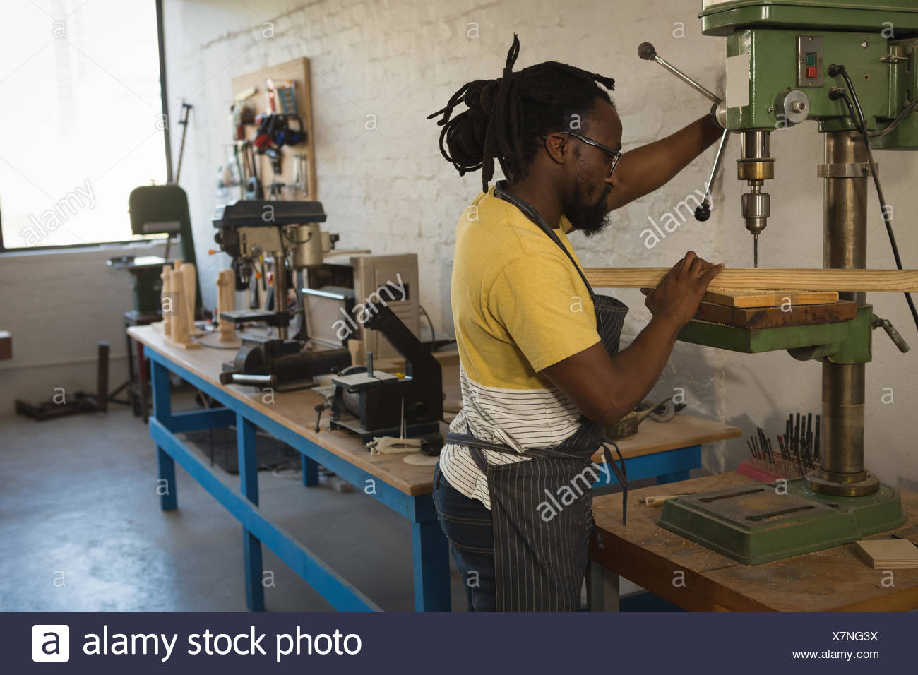 Carpenter drilling wooden plank with machine - Stock Image