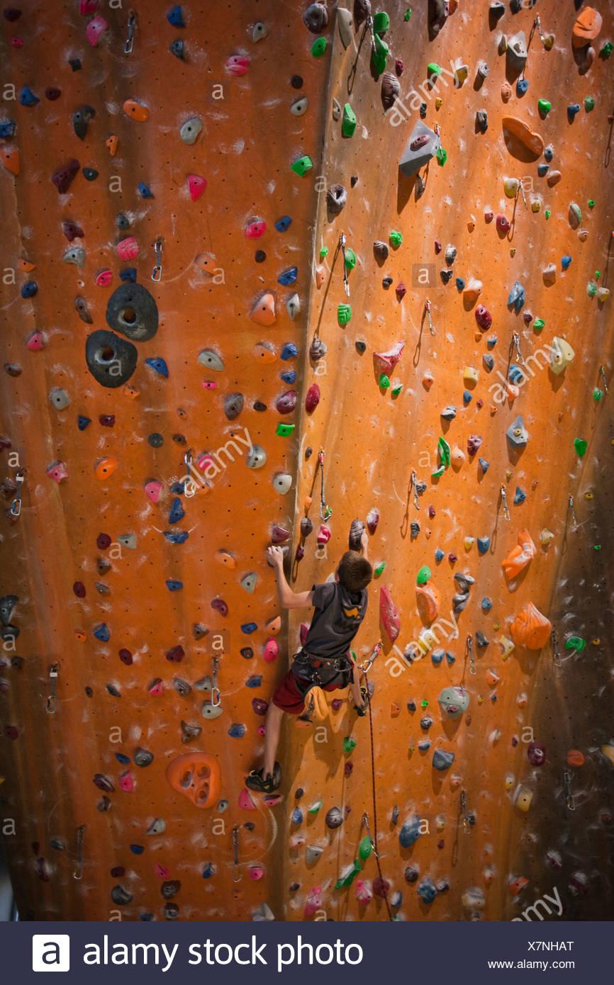 USA, Utah, Sandy, boy (12-13) on indoor climbing wall - Stock Image