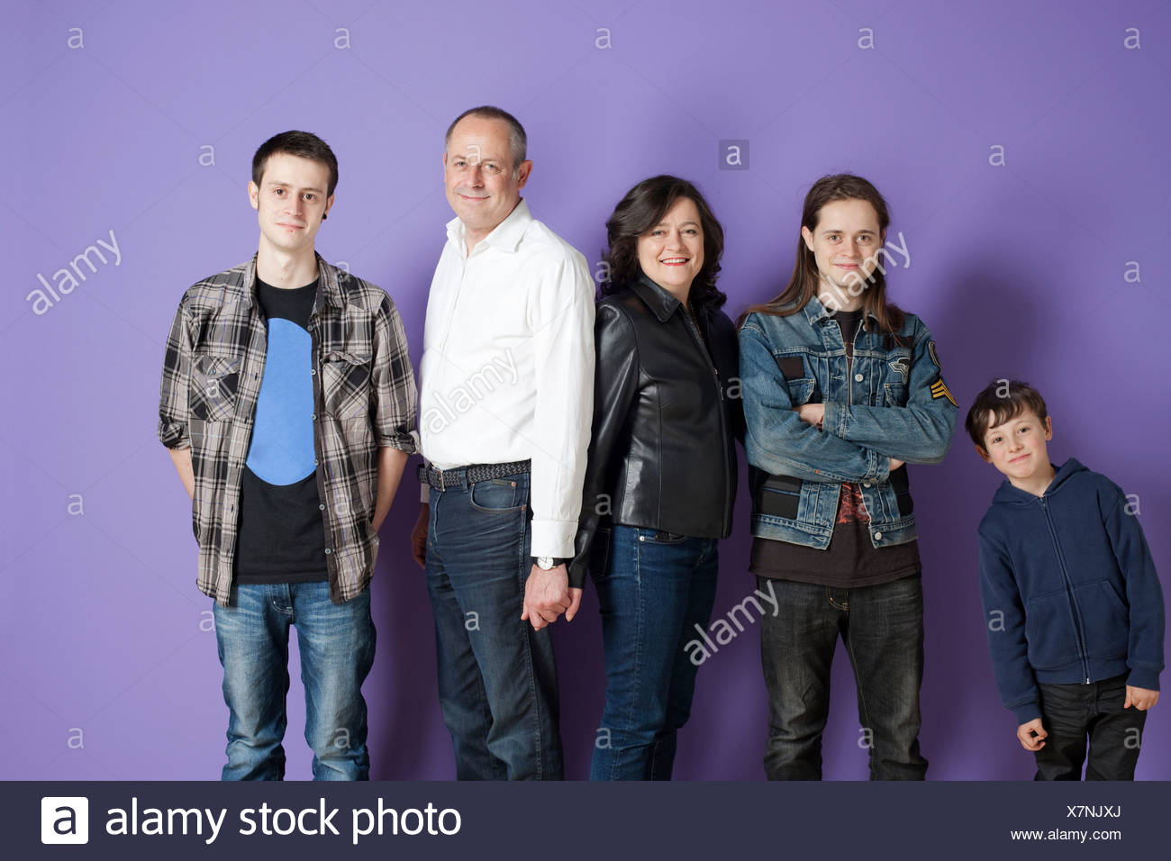 Portrait of family of five in front of purple background - Stock Image