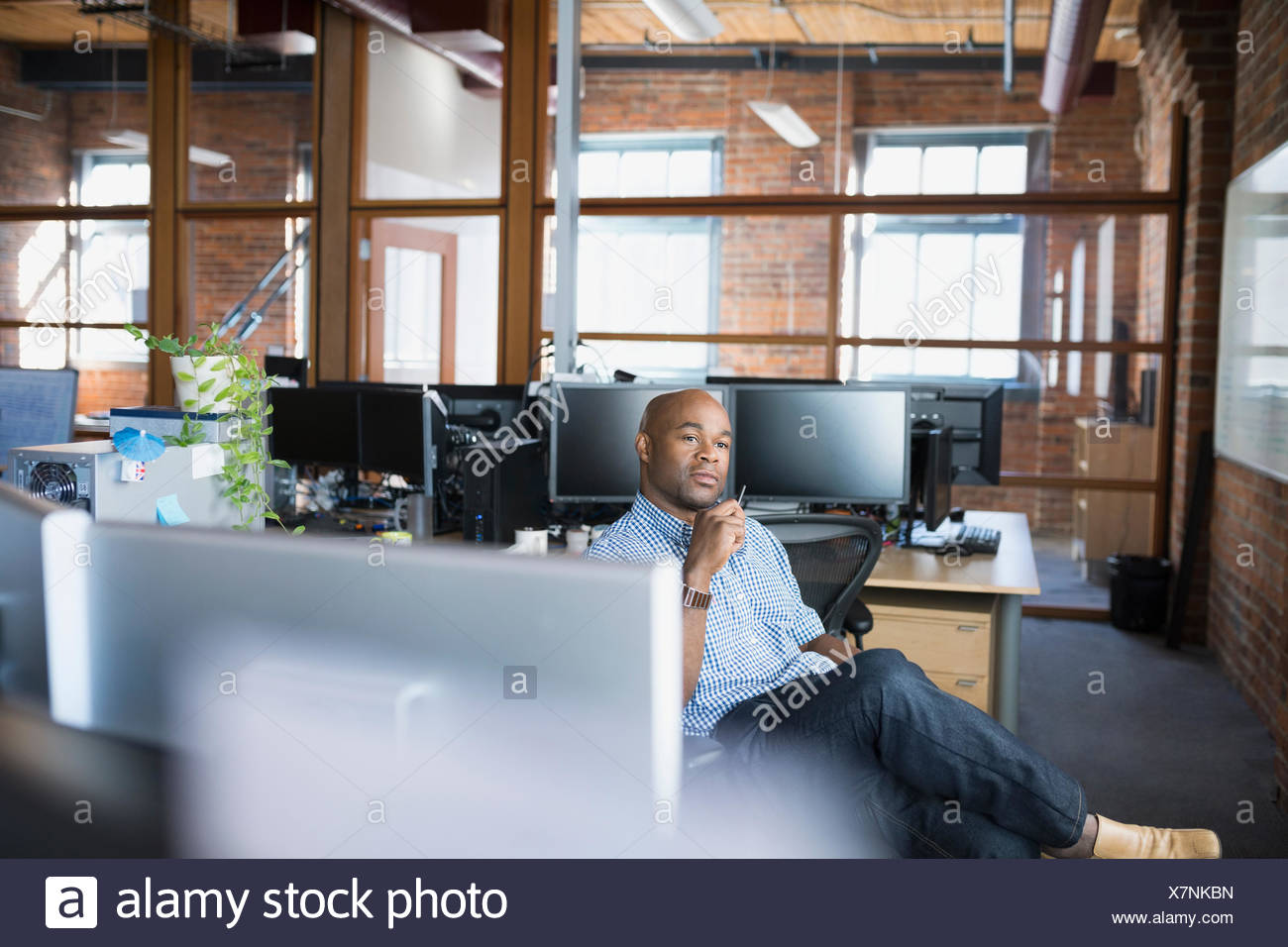 Pensive businessman in office - Stock Image