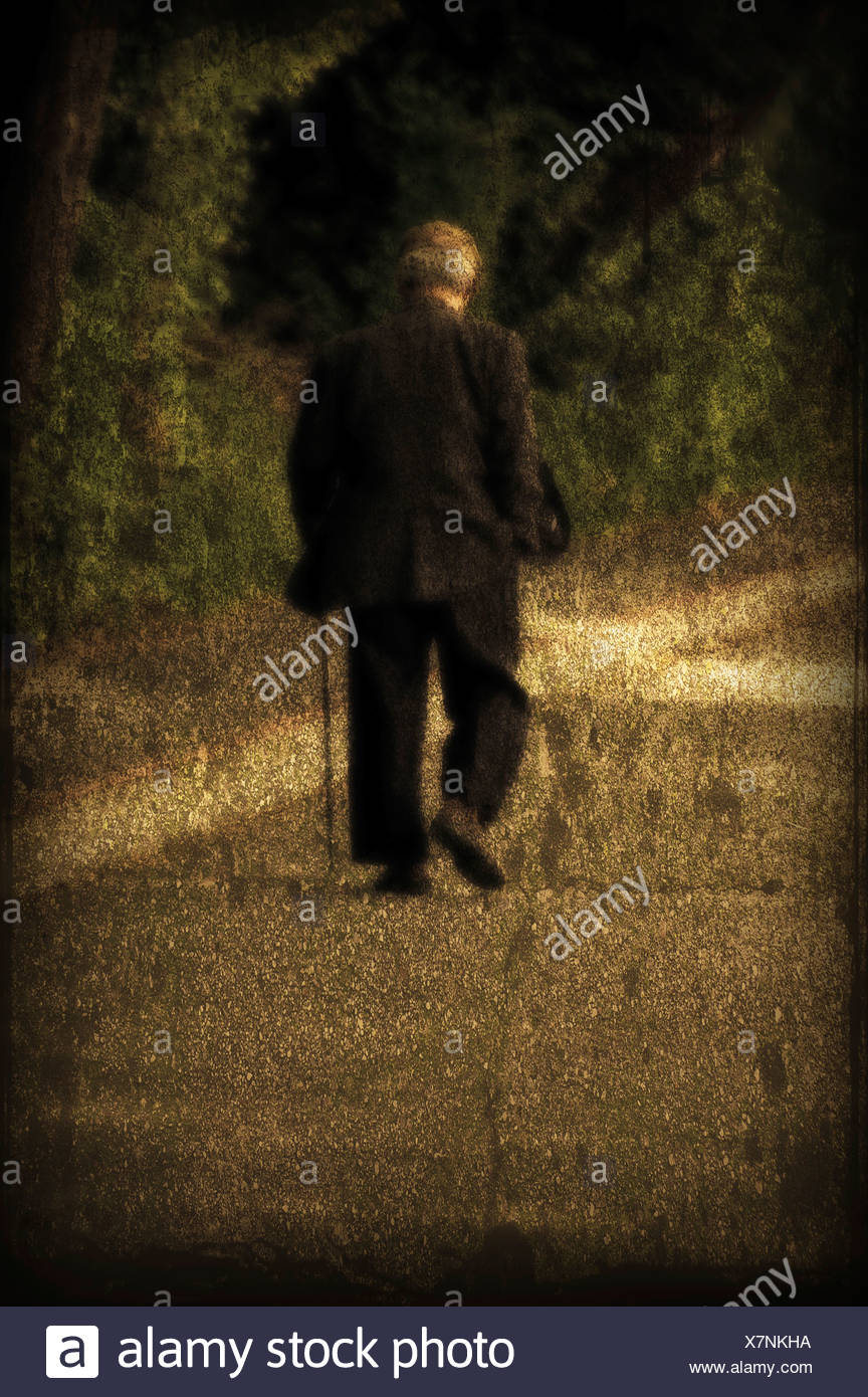 An elderly man with a cane walking along seawall. - Stock Image
