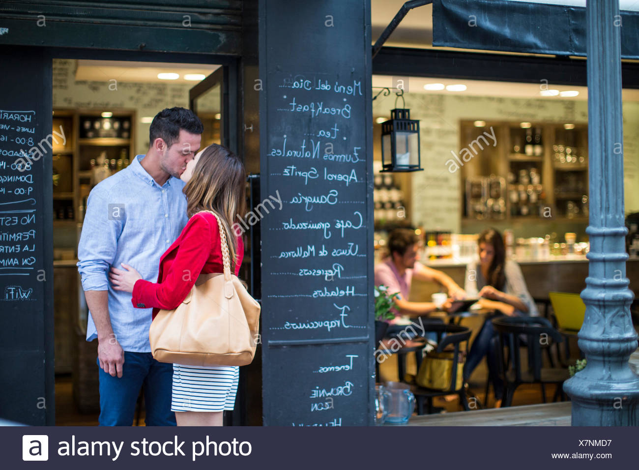 Romantic couple kissing outside cafe - Stock Image