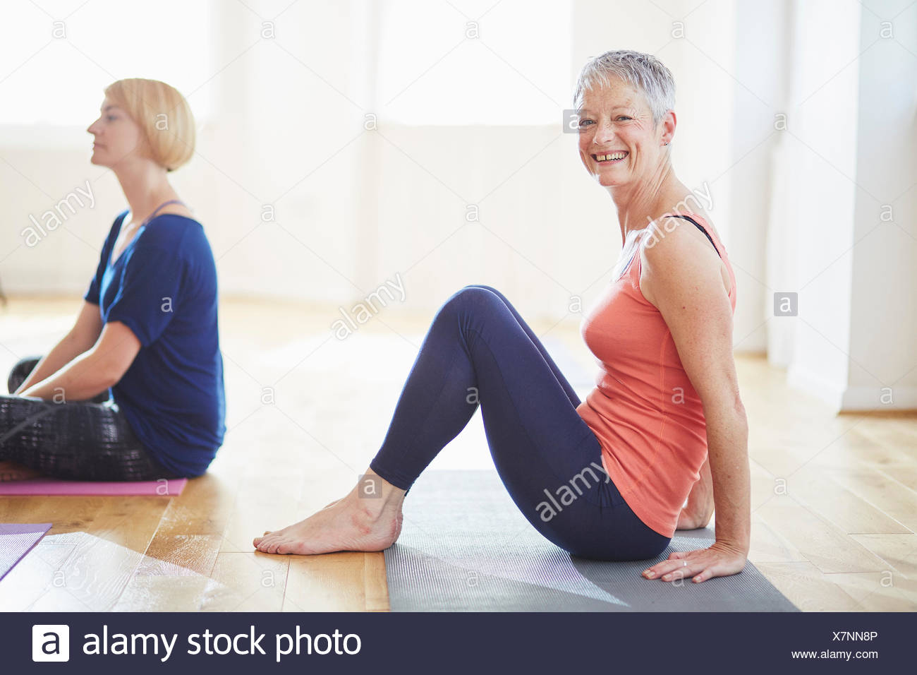 Portrait of mature woman sitting on floor in pilates class Stock Photo