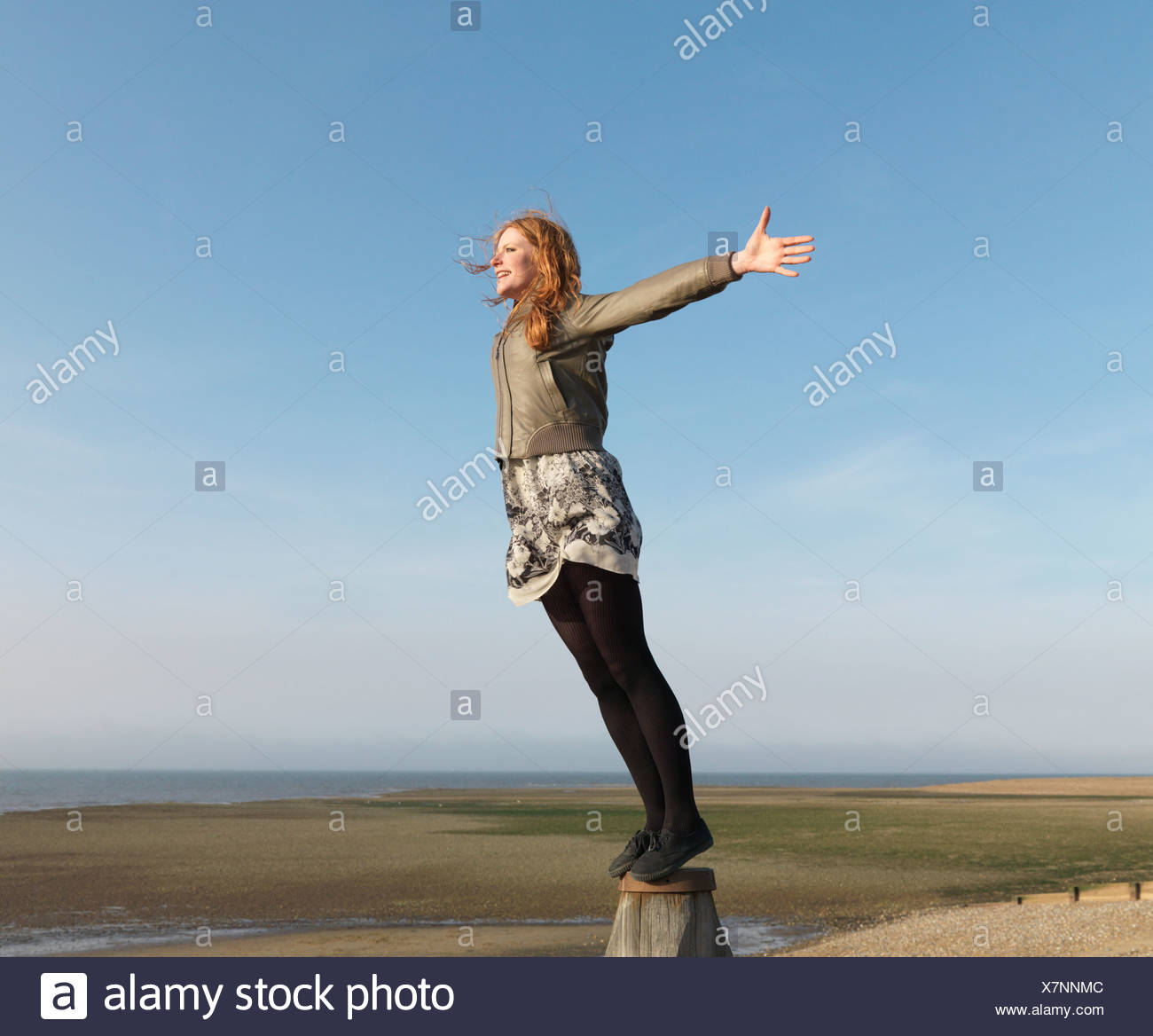 Woman standing on wooden post - Stock Image