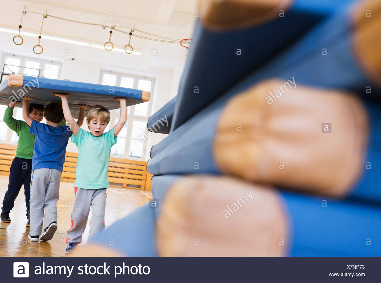 Boys carrying blue exercise mat above their heads - Stock Image