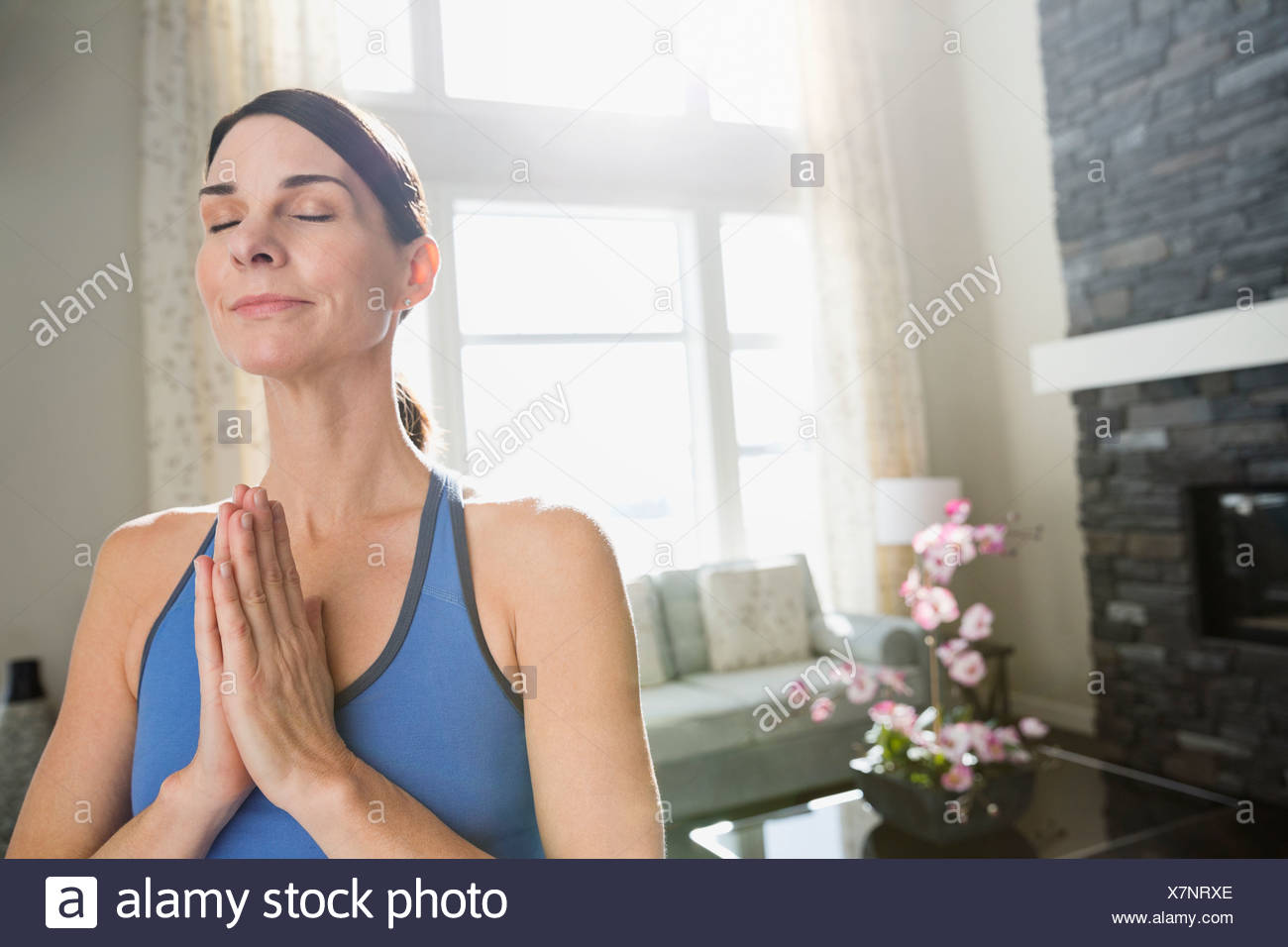 Mature woman with hands clasped meditating at home - Stock Image