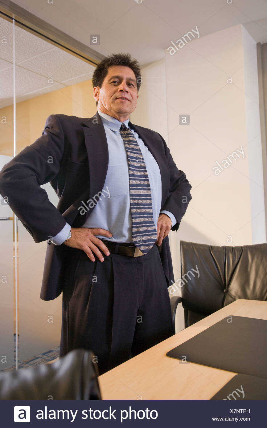 Hispanic businessman sitting by table with hand on hip in boardroom - Stock Photo