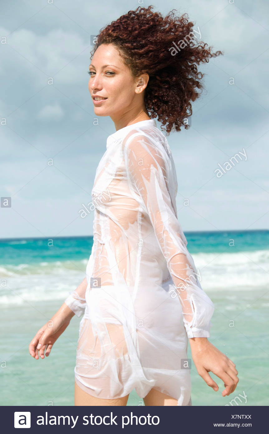 Young woman walking ocean, side view, Havana, Cuba - Stock Image
