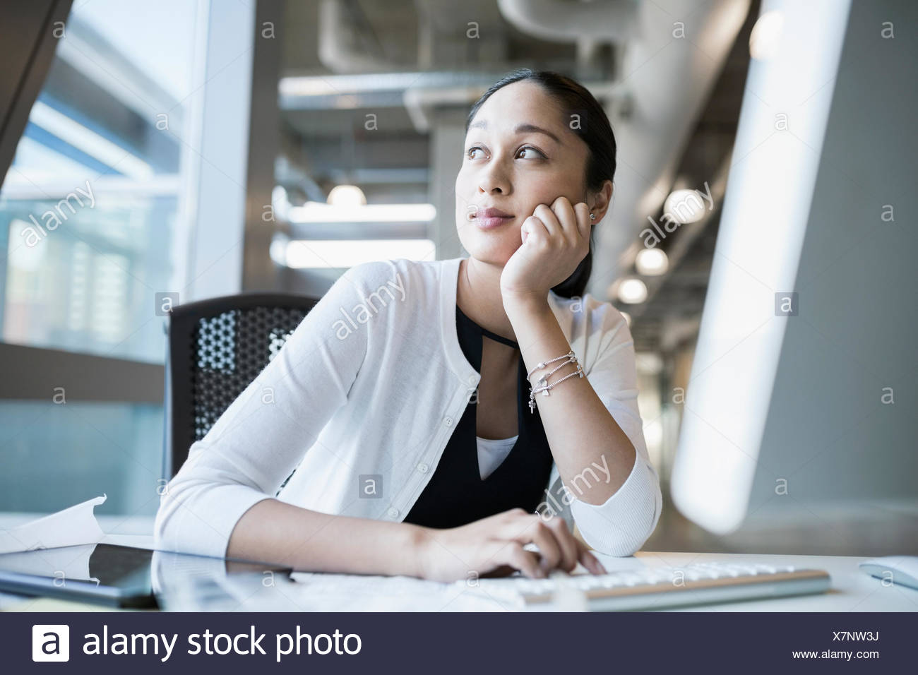 Pensive businesswoman looking out window - Stock Image