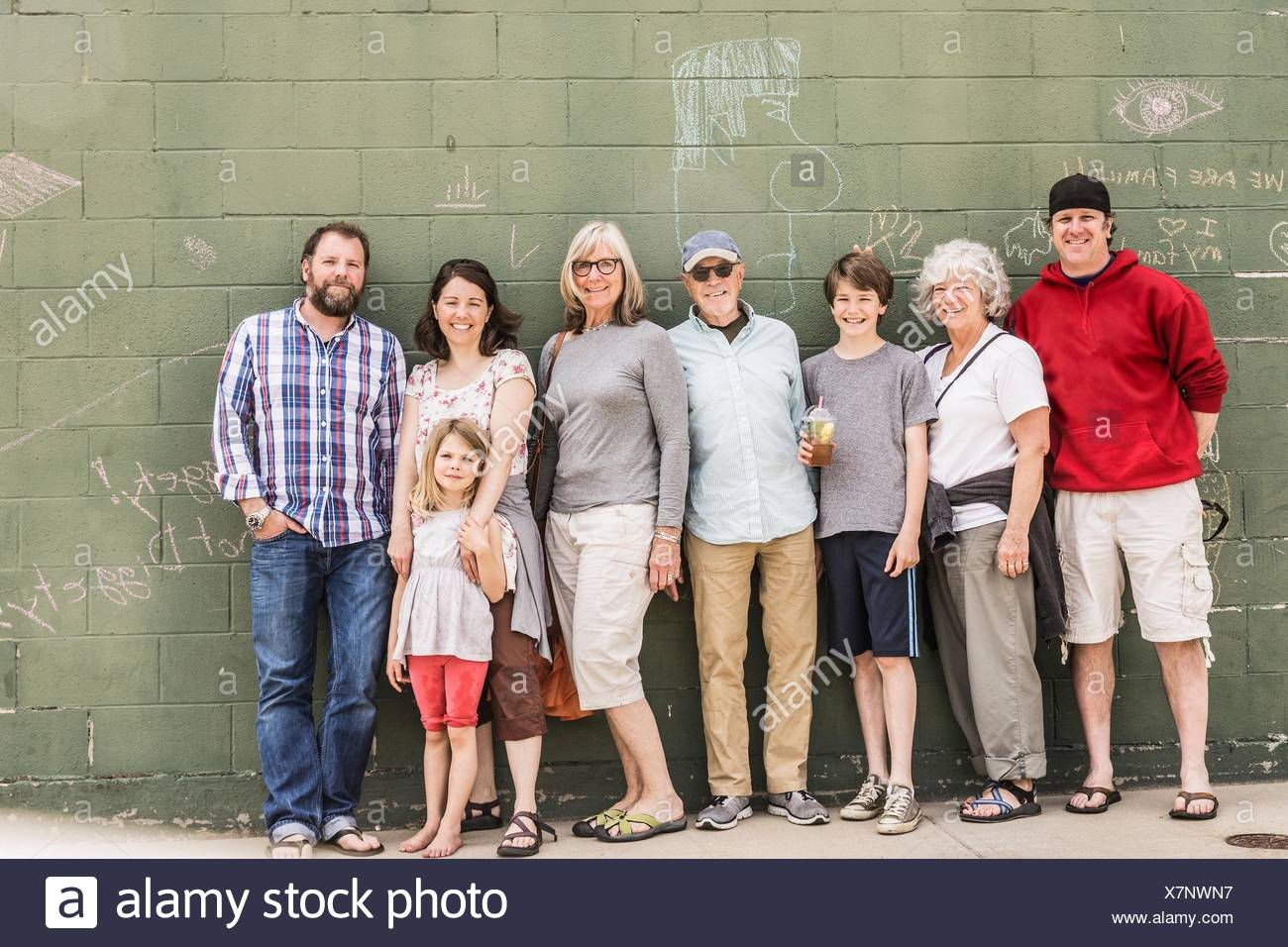 Three generation family in front of wall, portrait - Stock Image