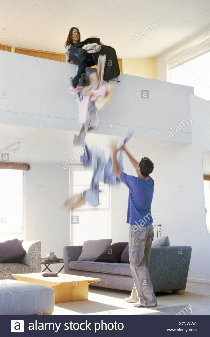 View of woman dumping clothes from a balcony onto boyfriend - Stock Image