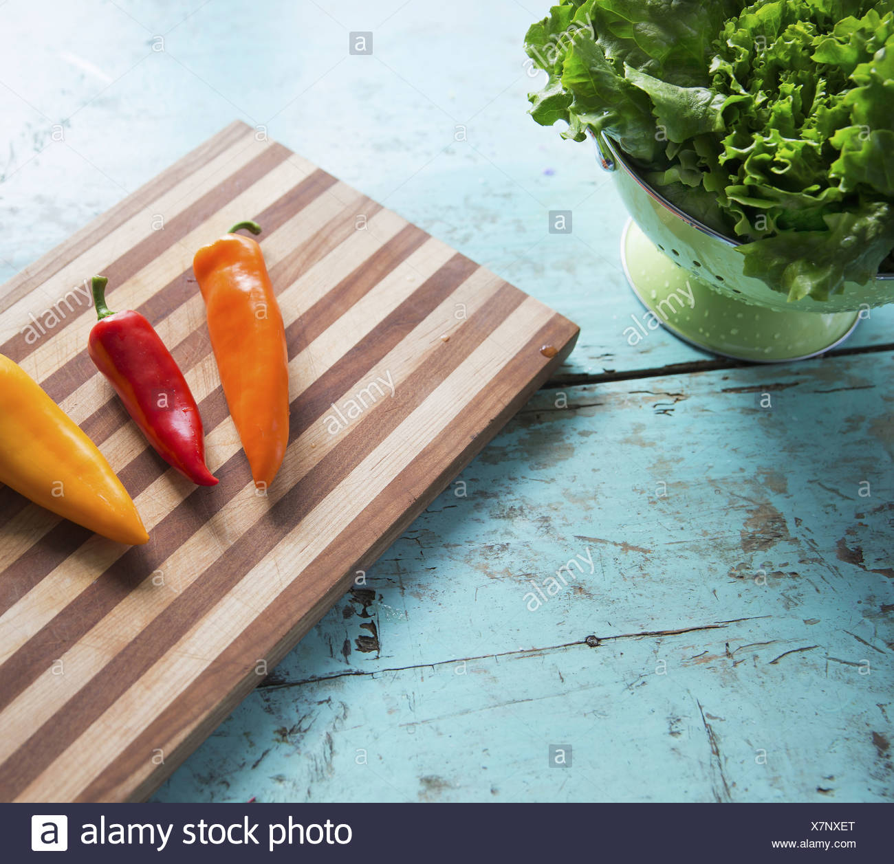A tabletop with a wooden chopping board and three sweet peppers and a bowl of salad leaves - Stock Image