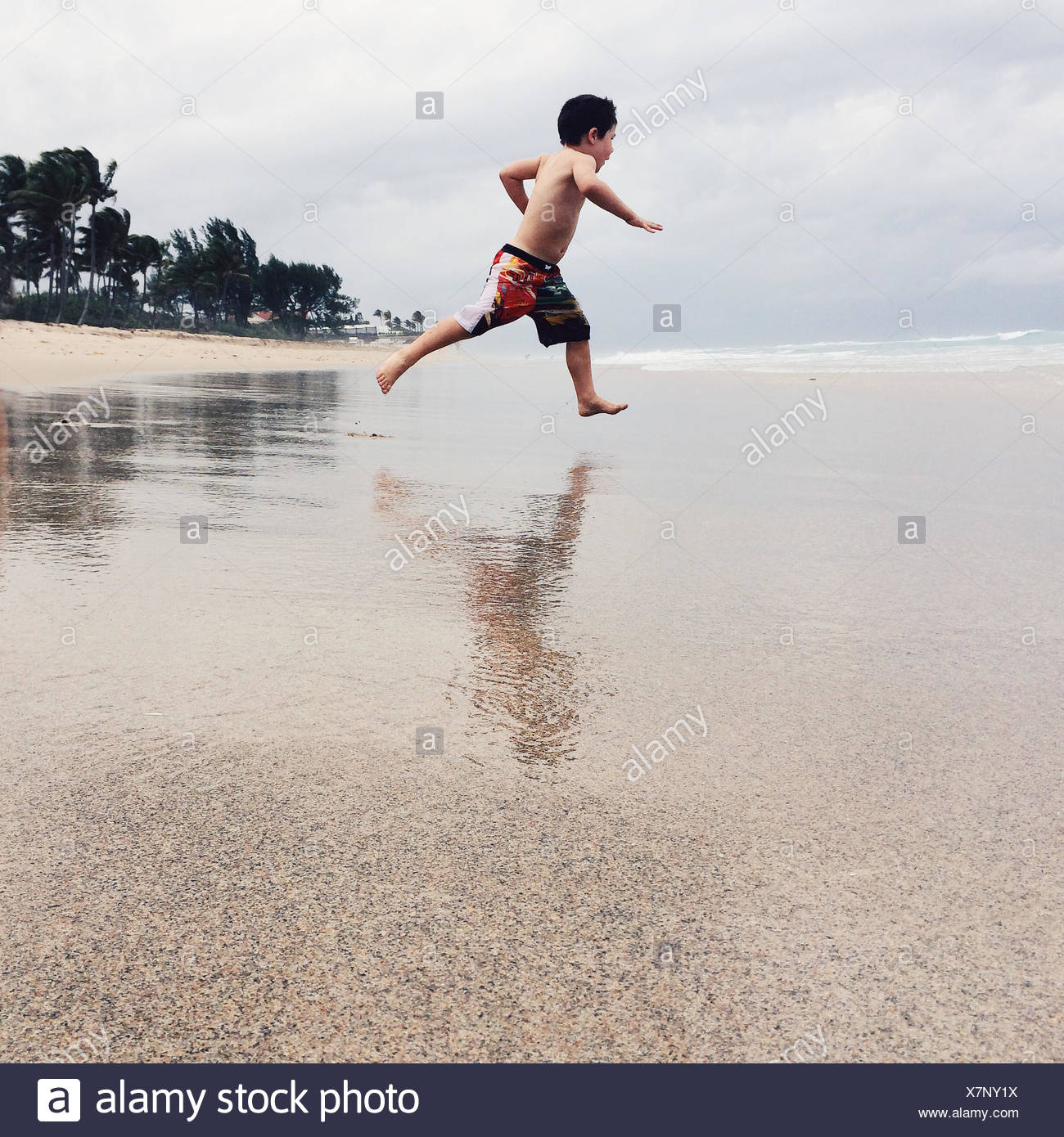 USA, Florida, Palm Beach County, West Palm Beach, Boy (2-3) running on beach - Stock Image