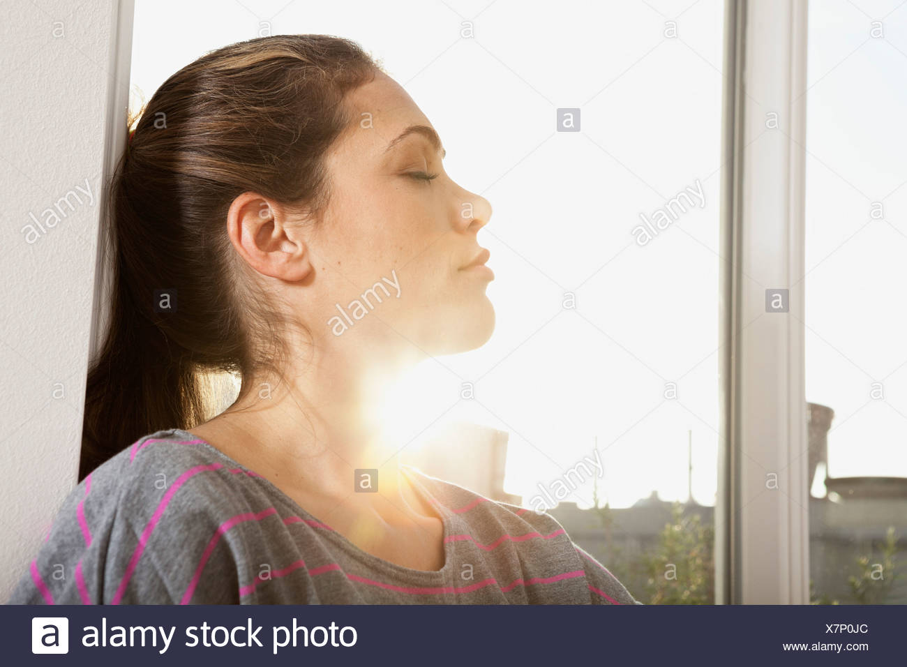 Portrait of woman standing at open window - Stock Image