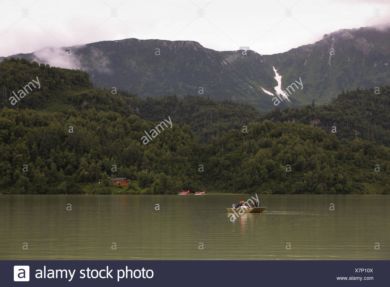 Fishermen in a small boat navigate water amongst a lush tree covered landscape. - Stock Image