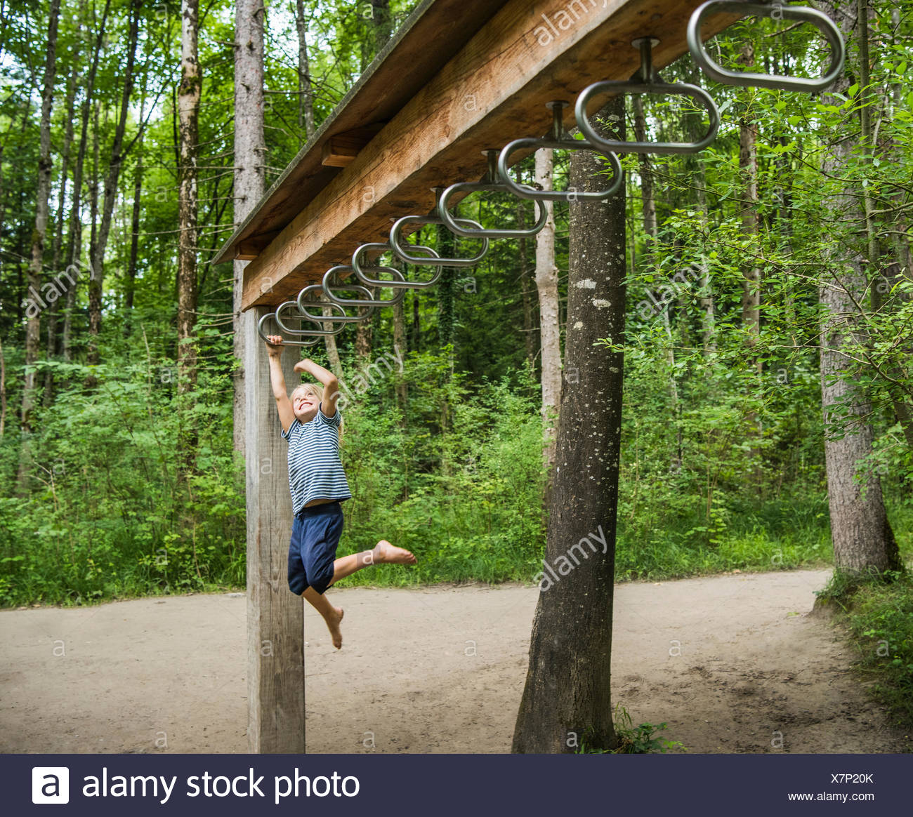 Boy hanging from monkey bars in playground - Stock Image