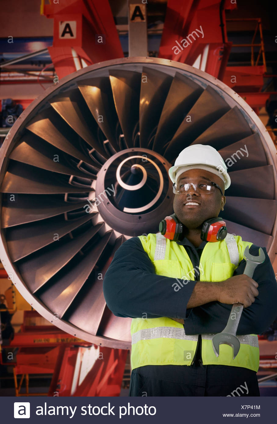 Aeronautic engineer standing in front of an airplane engine - Stock Image