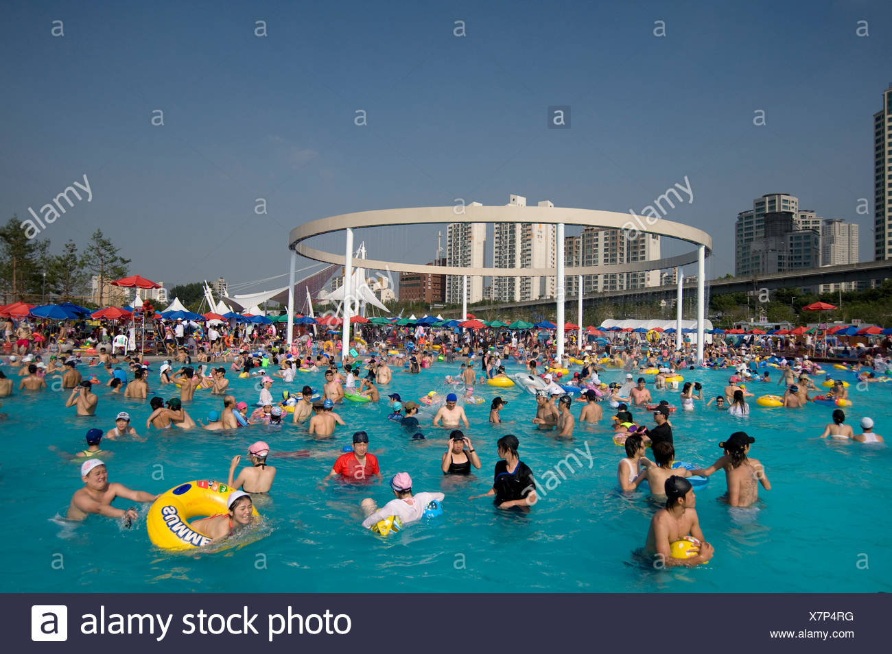 Throngs of people seek relief from the summer heat at the local pool. - Stock Image