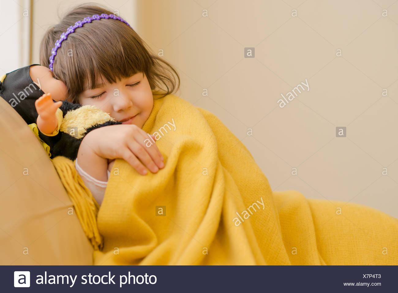 Young girl lying on sofa pretending to sleep - Stock Image