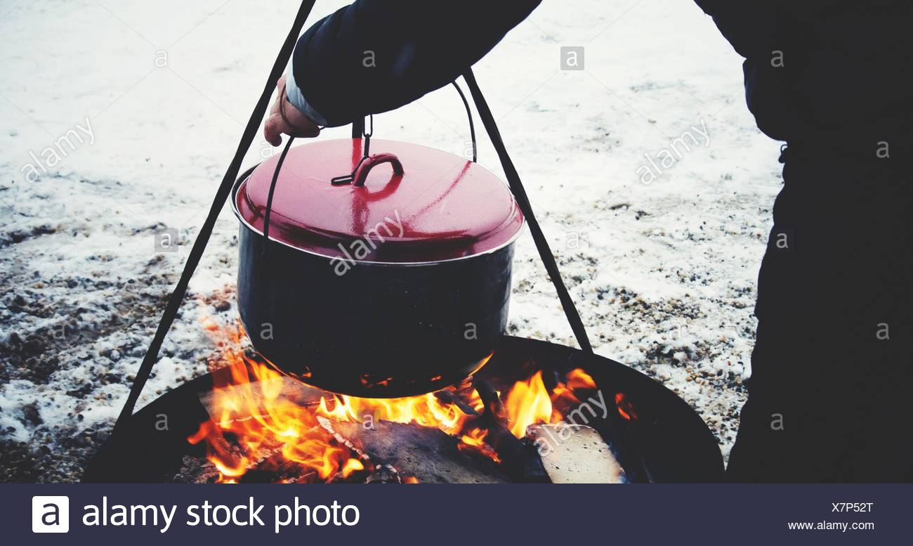 Cropped Image Of Man Heating Cooking Utensil Outdoors During Winter - Stock Image