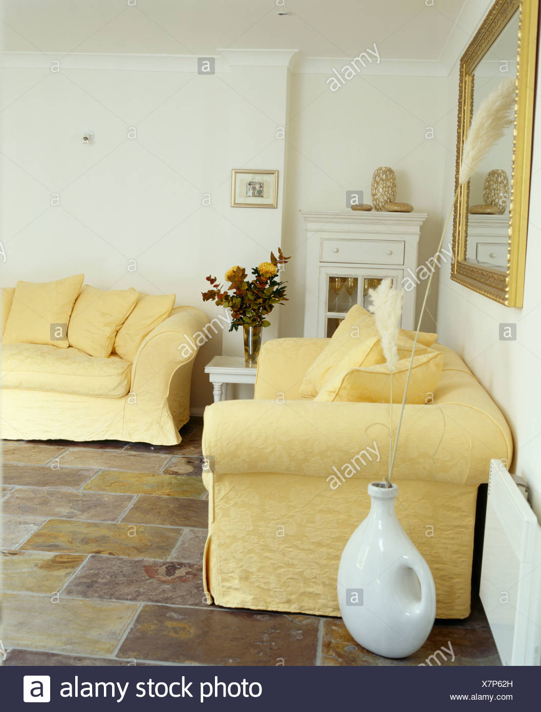Pale yellow sofas sofas in white living room with slate floor tiles ...