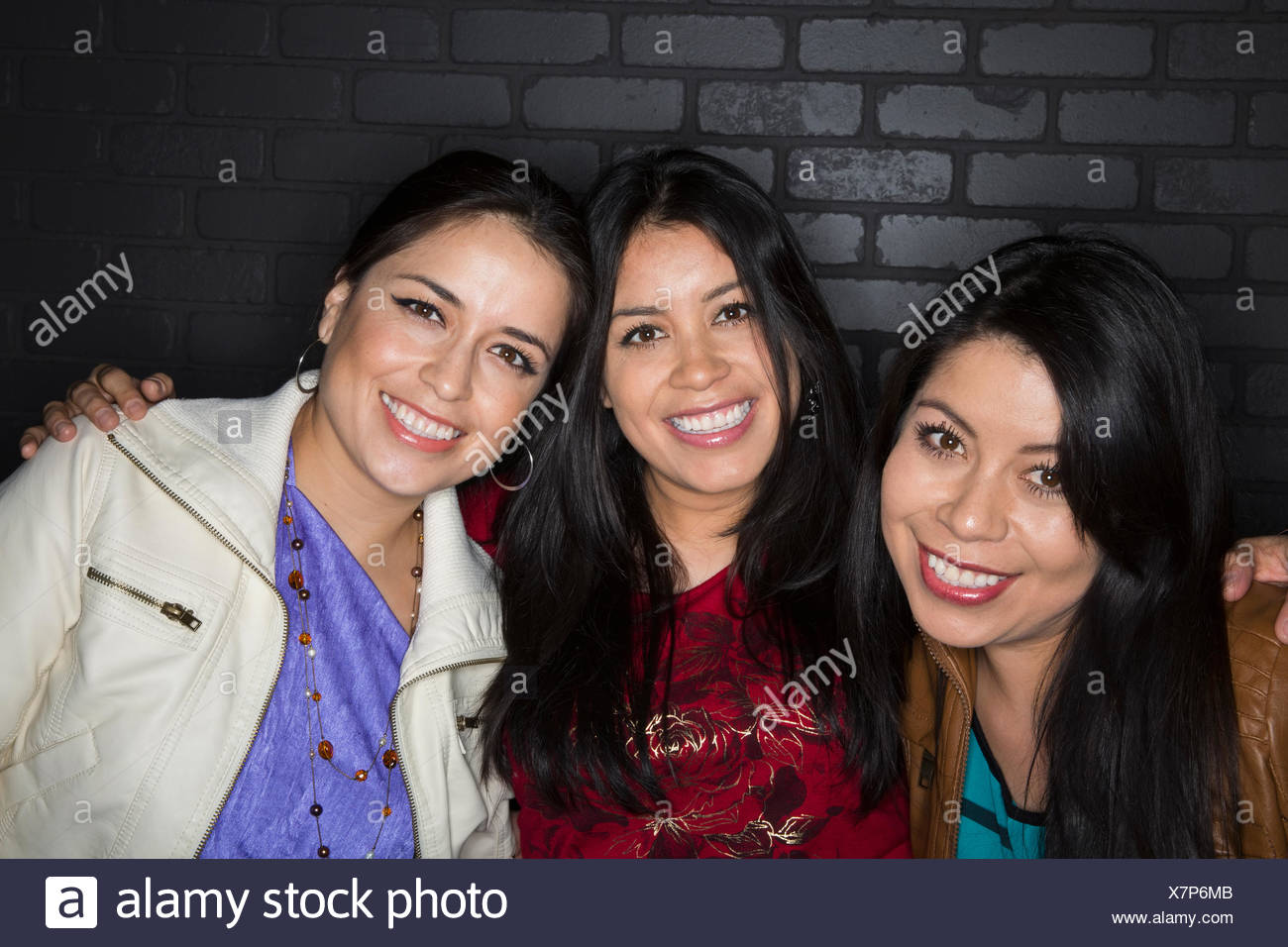 Portrait of smiling sisters hugging - Stock Image