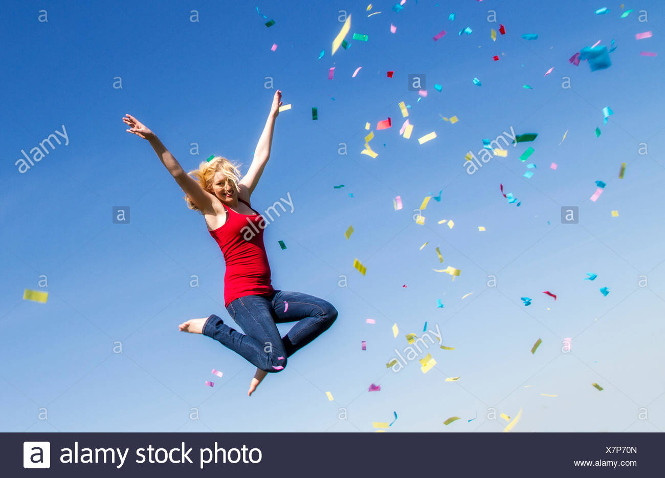 Young woman jumping with confetti - Stock Image