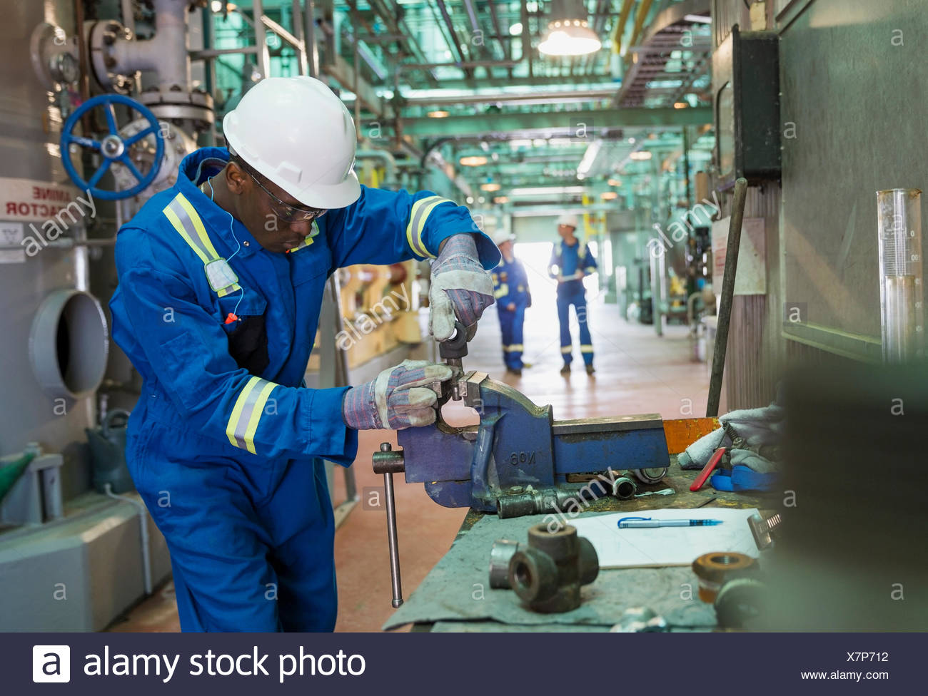 Male worker using vise grip in gas plant - Stock Image