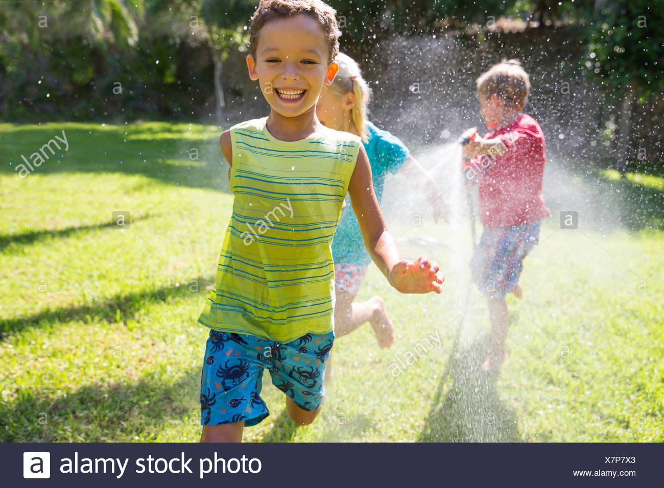 Three children chasing each other in garden with water sprinkler - Stock Image