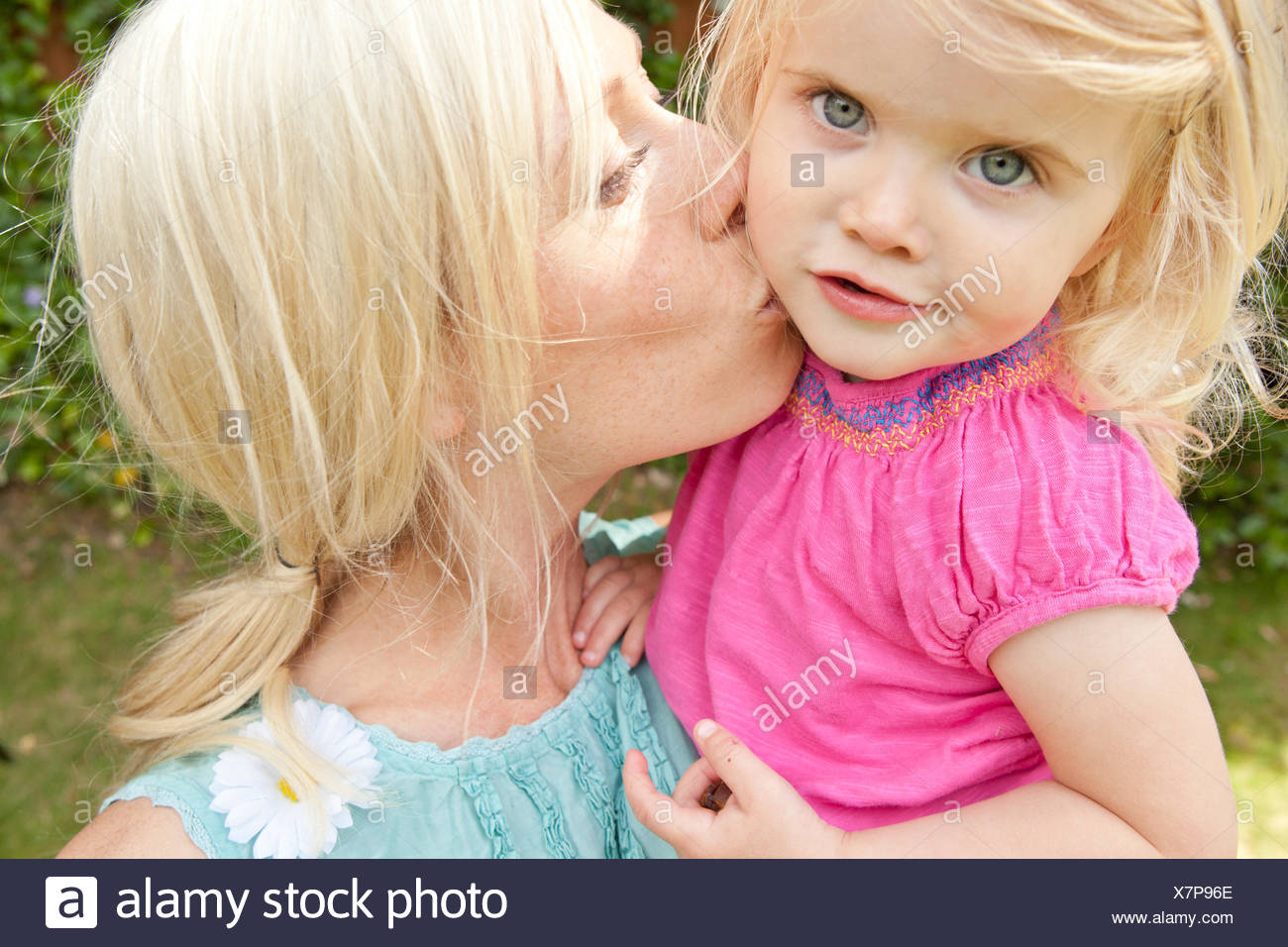 Close up of young adult mother kissing toddler daughter in garden Stock Photo