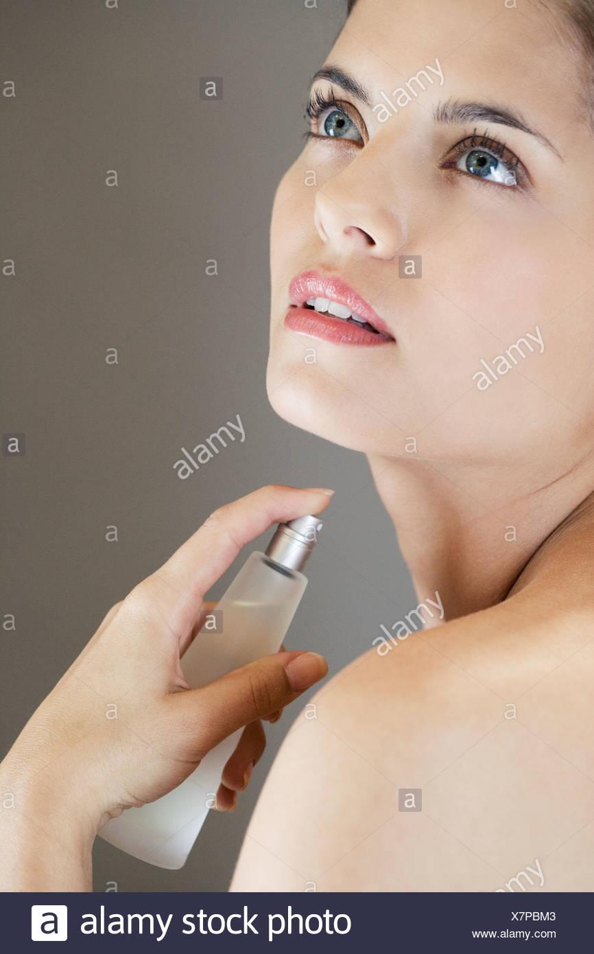 Woman spraying perfume onto her neck - Stock Image
