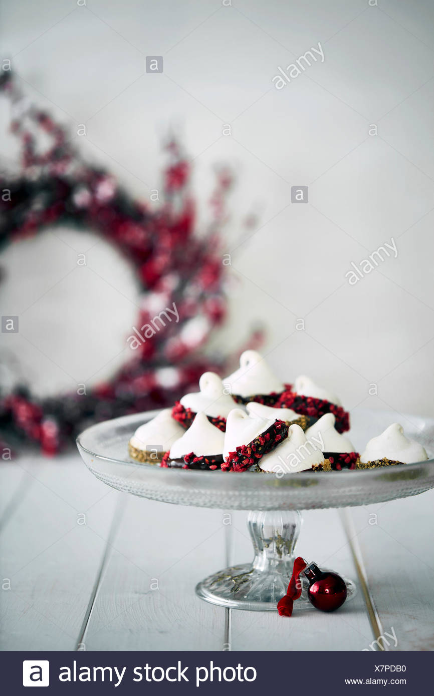 Christmas decorations and meringues on cake stand - Stock Image