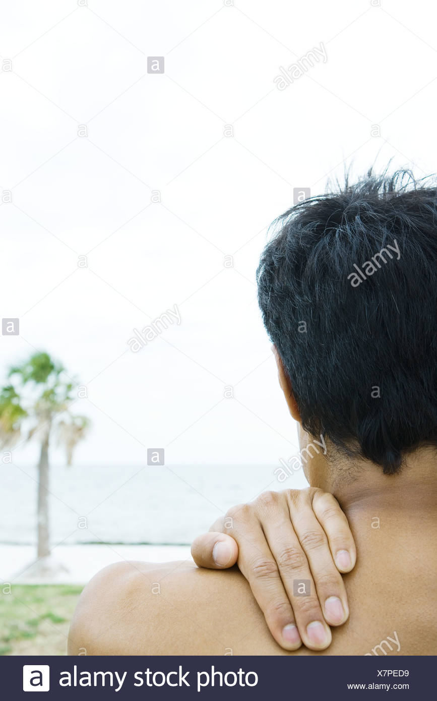 Man at the beach, hand on shoulder, cropped rear view - Stock Image