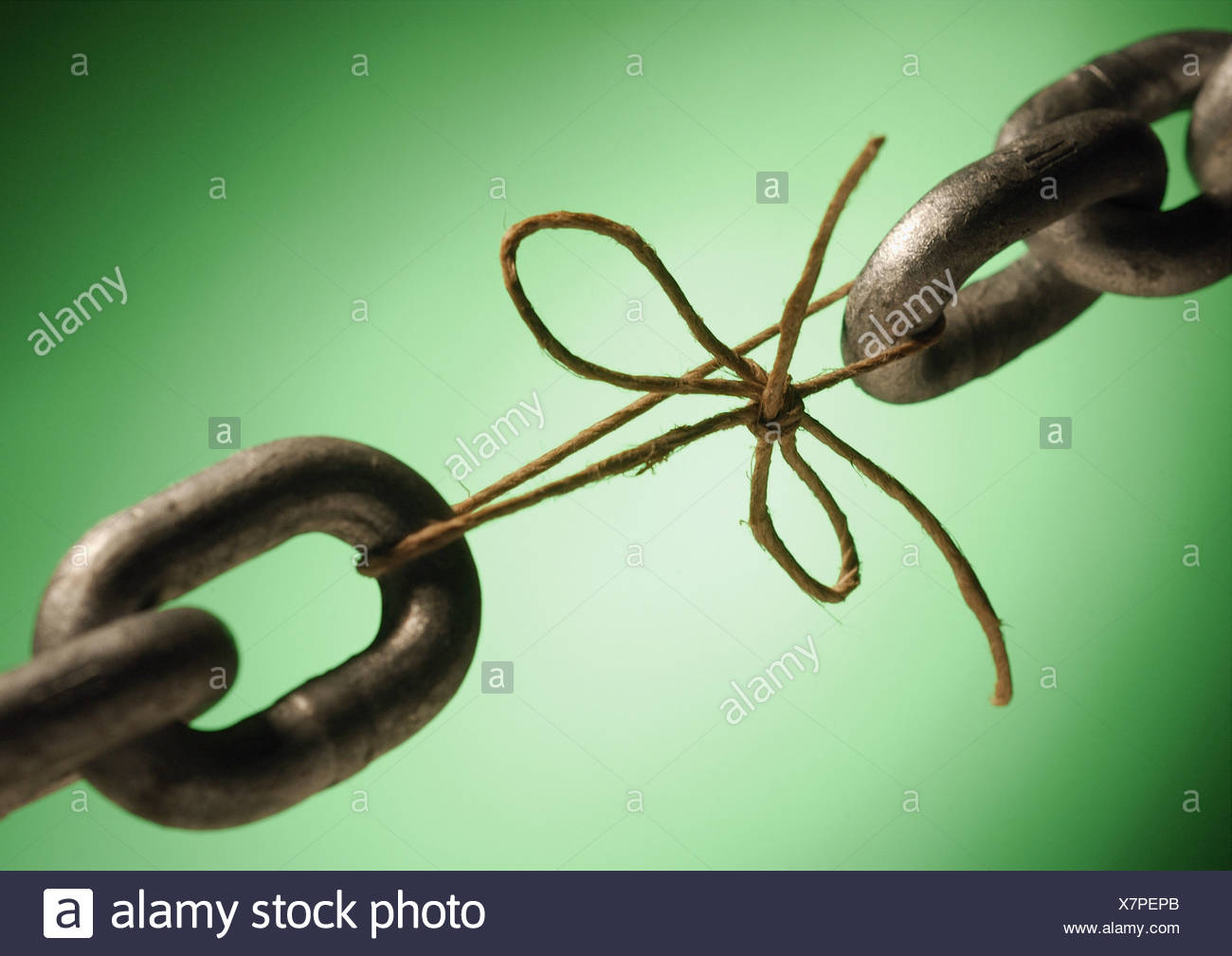 Two ends of a chain linked by string, close-up - Stock Image