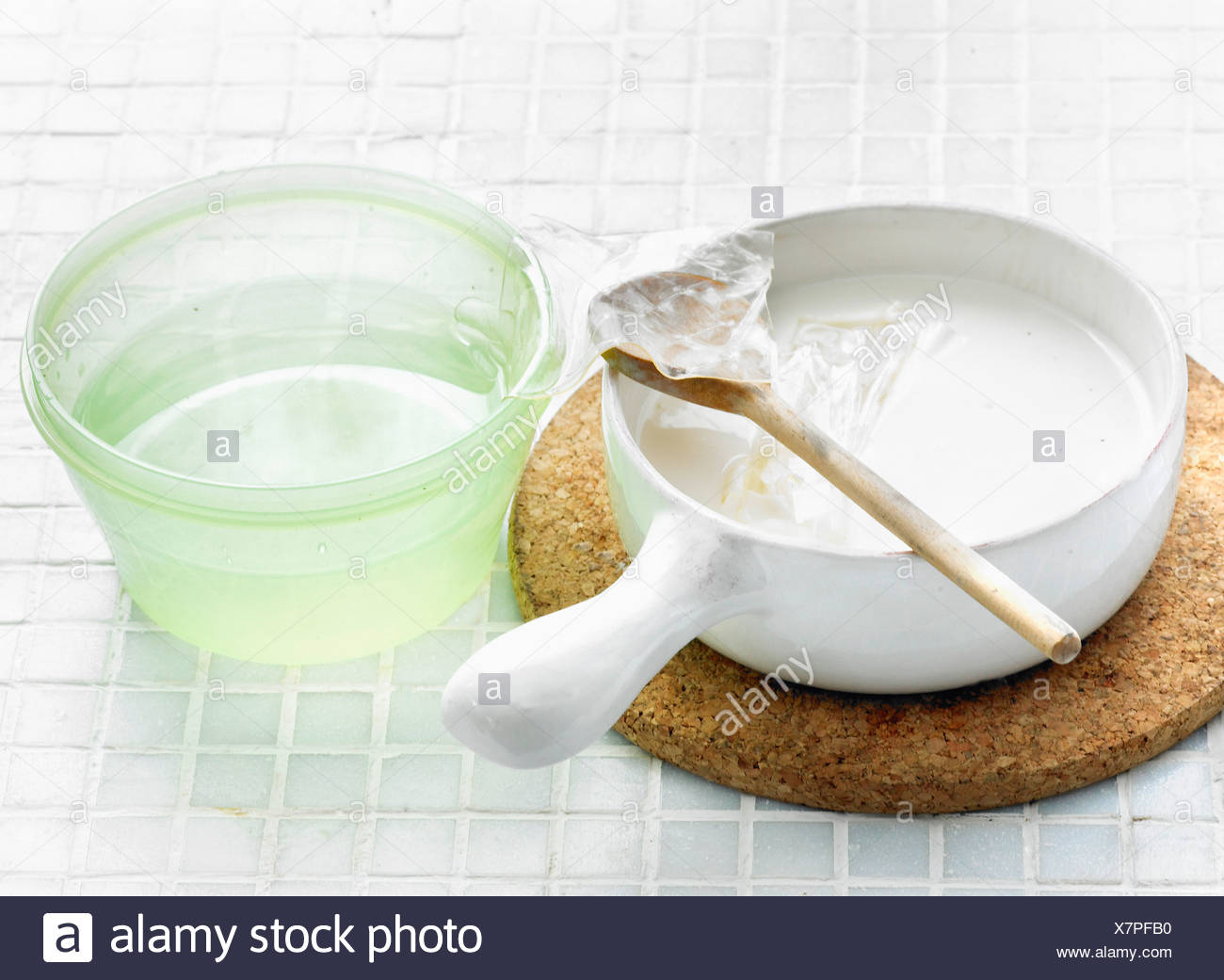 Adding the gelatine sheets to the hot cream and sugar mixture - Stock Image