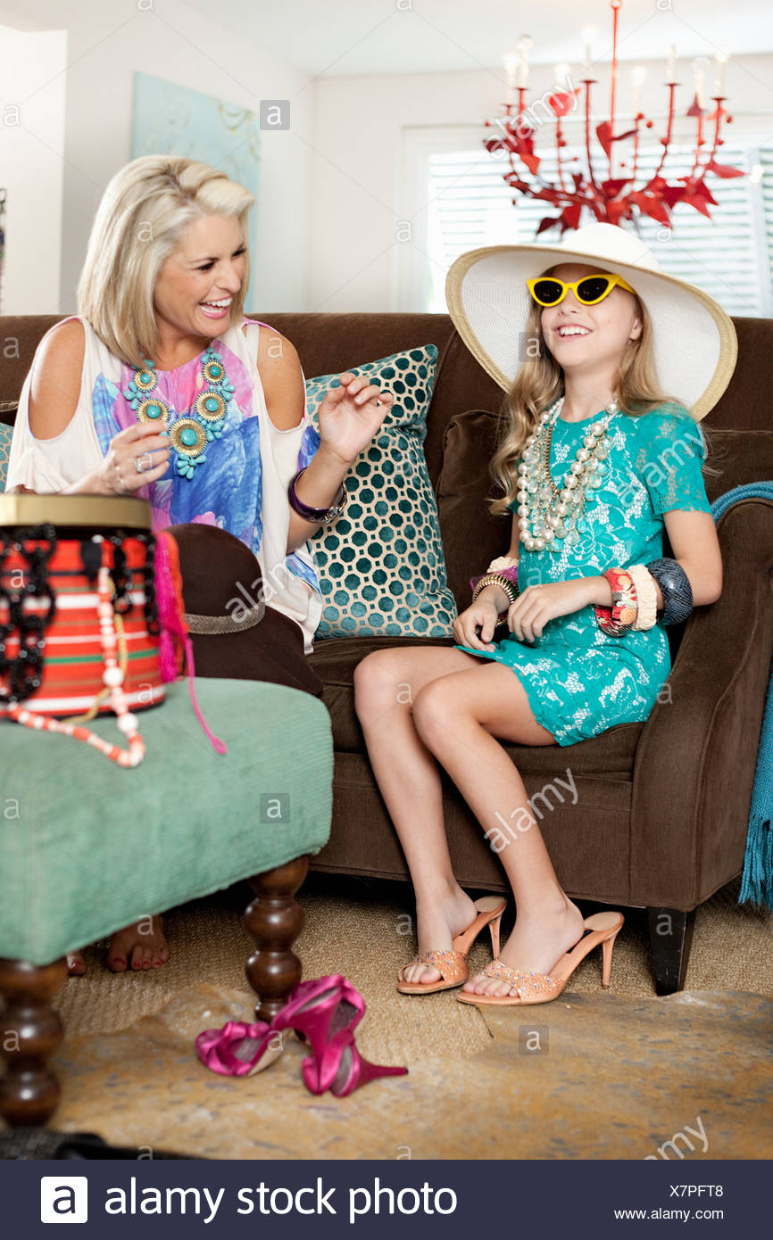 Mother dressing up daughter in hat and high heels - Stock Image