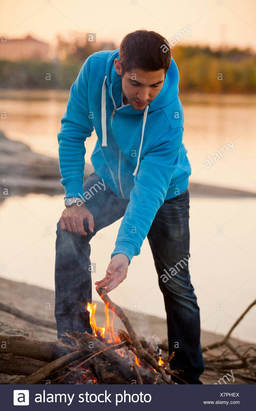 Young man arranging firewood at campfire, Osijek, Croatia - Stock Image