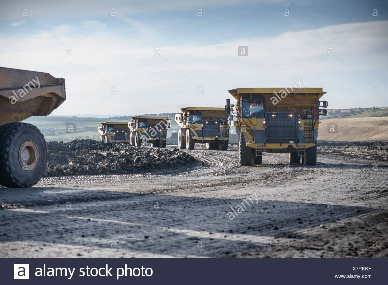 Trucks with coal rocks at surface mine - Stock Image