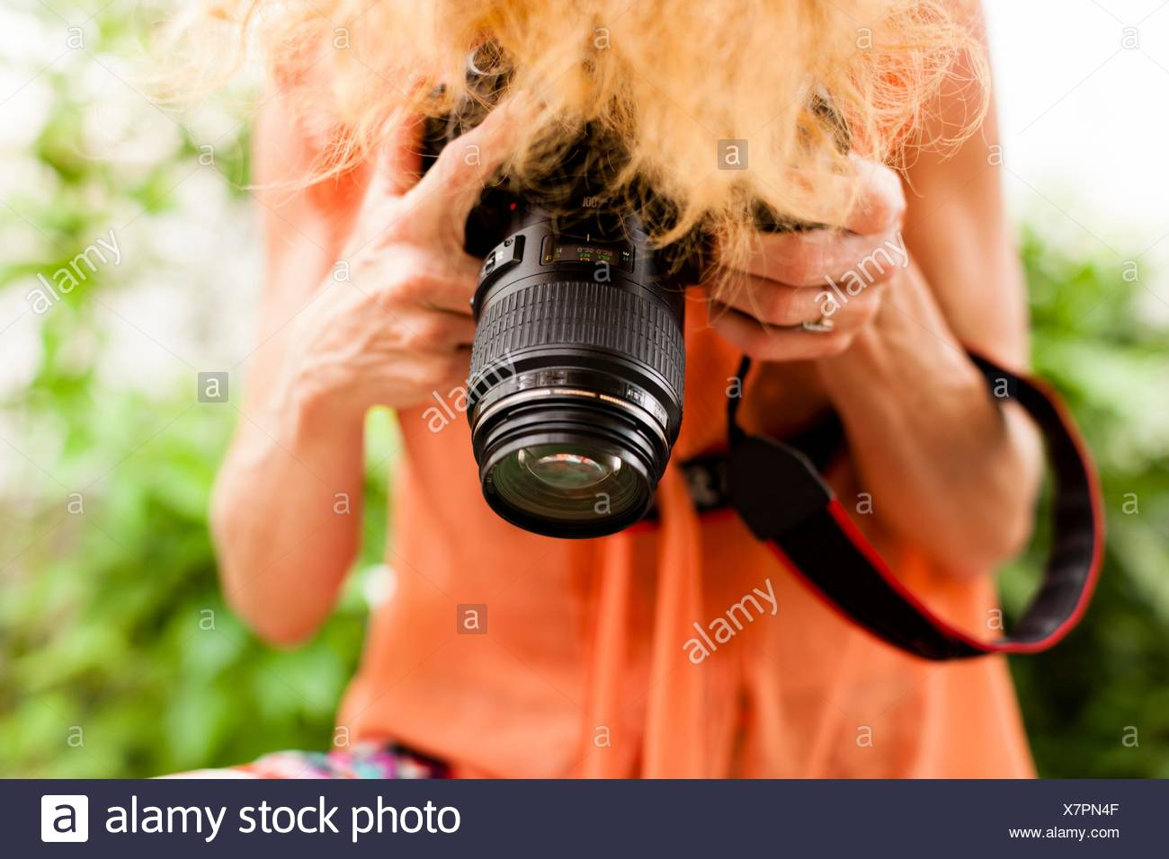 Cropped shot of woman with red hair photographing downward with digital SLR - Stock Image
