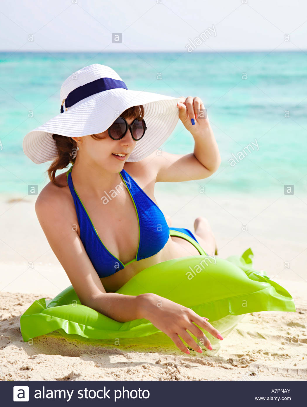 Teenage girl in a bikini sunbathing on the beach - Stock Image