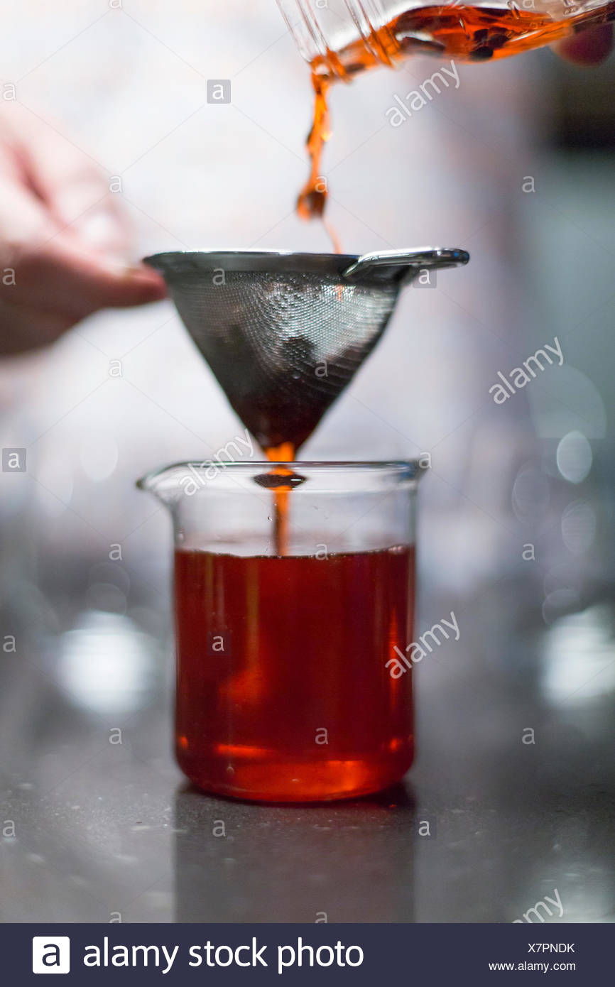 Person mixing drinks through a seive - Stock Image