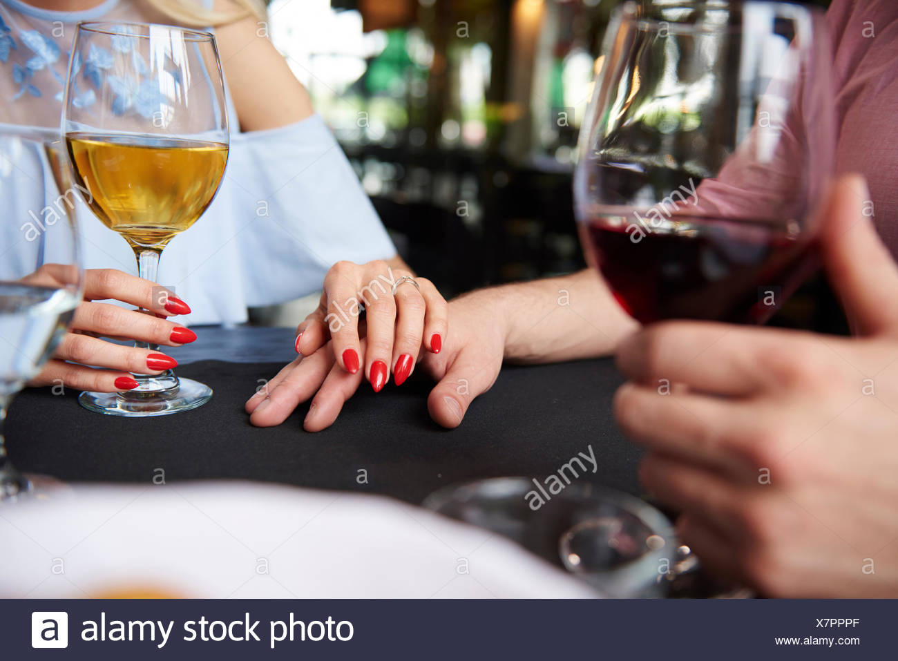 Cropped view of woman's hand on boyfriend's hand at restaurant table - Stock Image