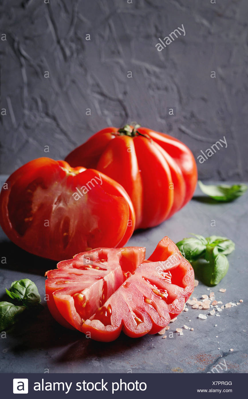 Whole and sliced organic tomatoes Coeur De Boeuf. Beefsteak tomato with pink salt and basil on blue gray metal texture background. Close up with space - Stock Image