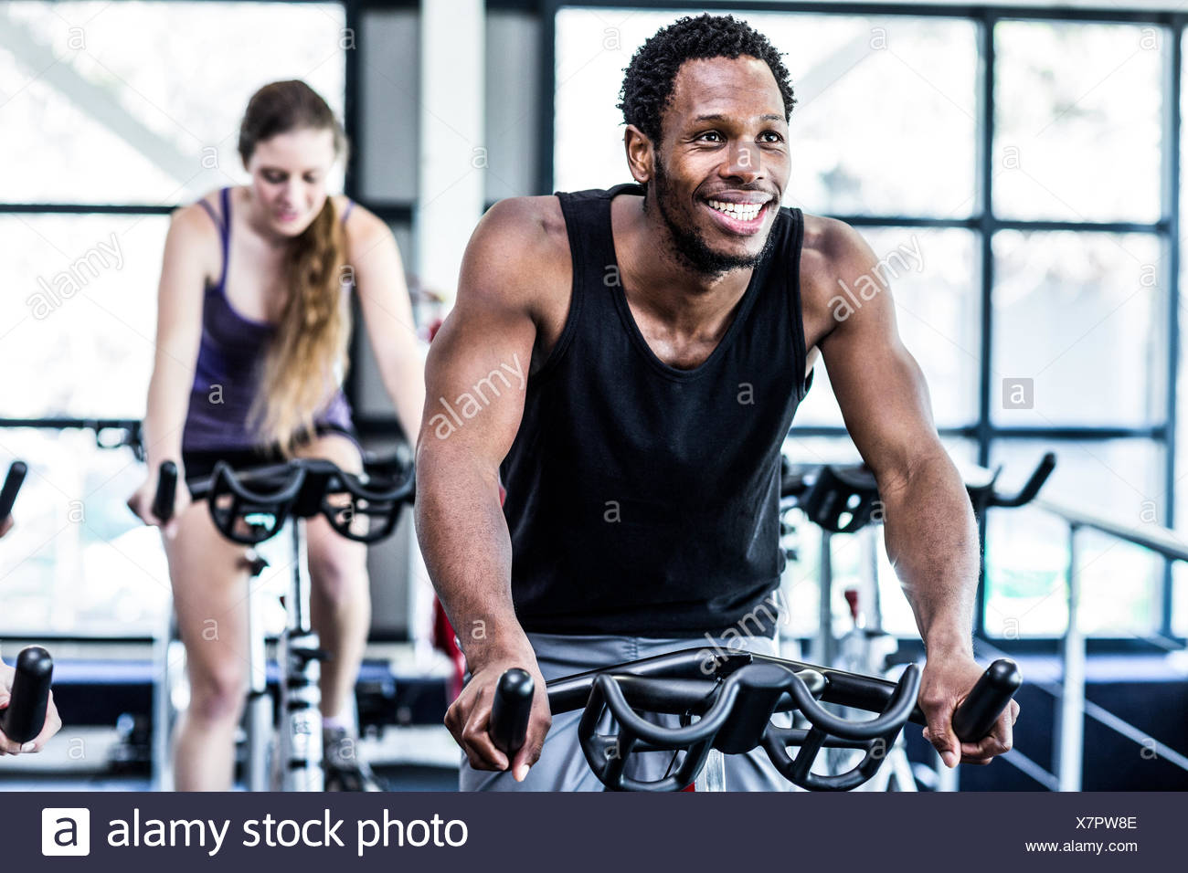 Fit man working out at spinning class - Stock Image