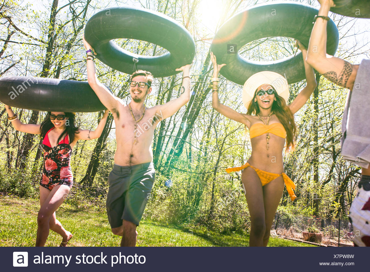 People carrying inner tubes above heads, laughing - Stock Image