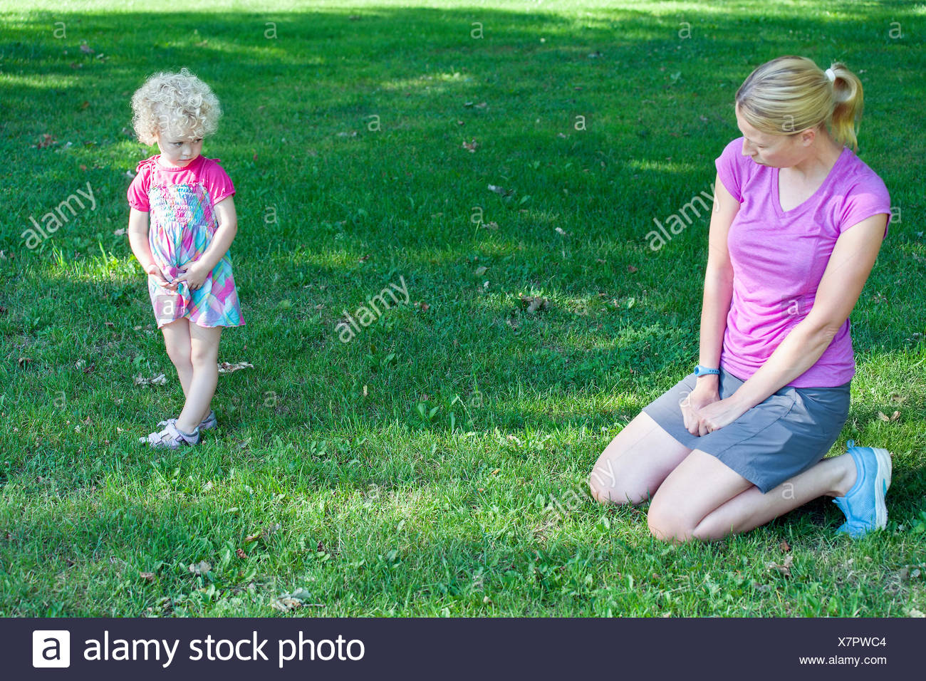 Mother copying daughter's (4-5) facial expression - Stock Image