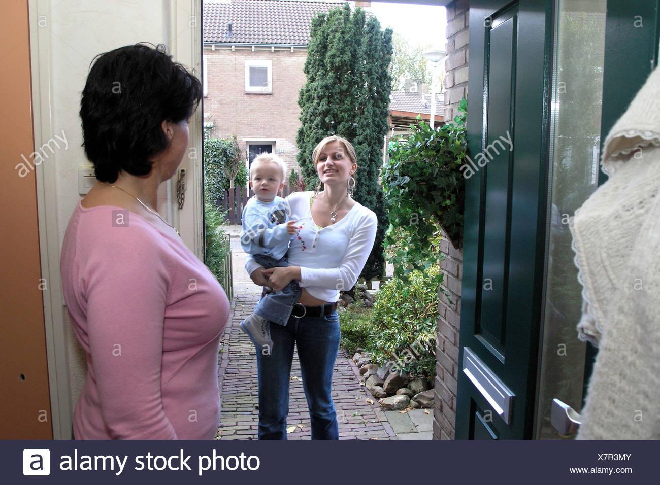 Daughter in law visit mother in law, standing at frontdoor talking on doorstep - Stock Image