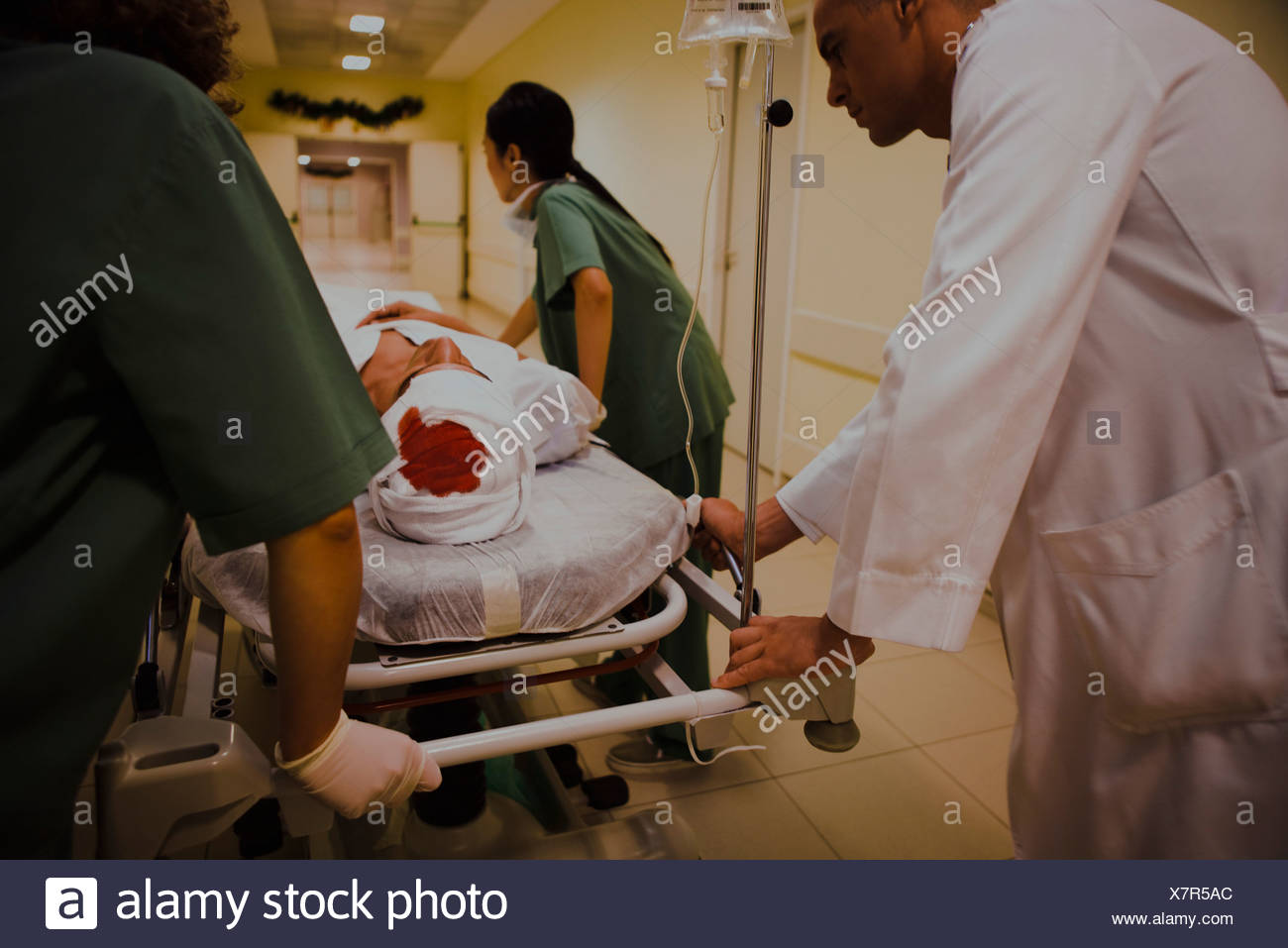 Healthcare workers transporting injured patient on gurney, cropped - Stock Image