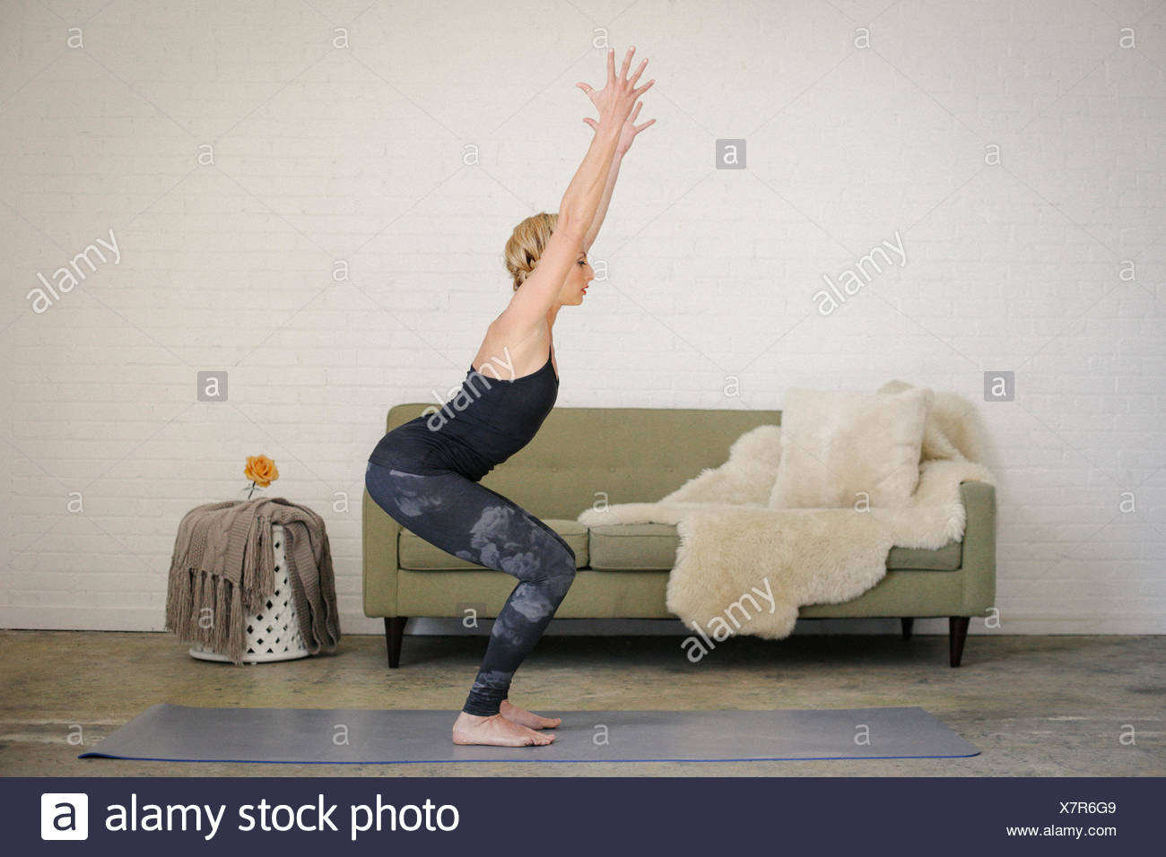 A blonde woman in leotard and leggings, standing on a yoga mat in a room, doing yoga, squatting down with her arms raised. - Stock Image